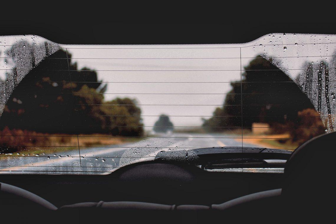Blick aus der Heckscheibe eines Autos auf eine verregnete Straße mit Bäumen rechts und links.