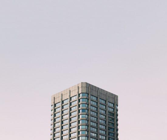 Die oberen Stockwerke eines Hochhauses vor einem klaren, zartrosa Himmel. Symbolbild für das Kolloquium Wärmewende.