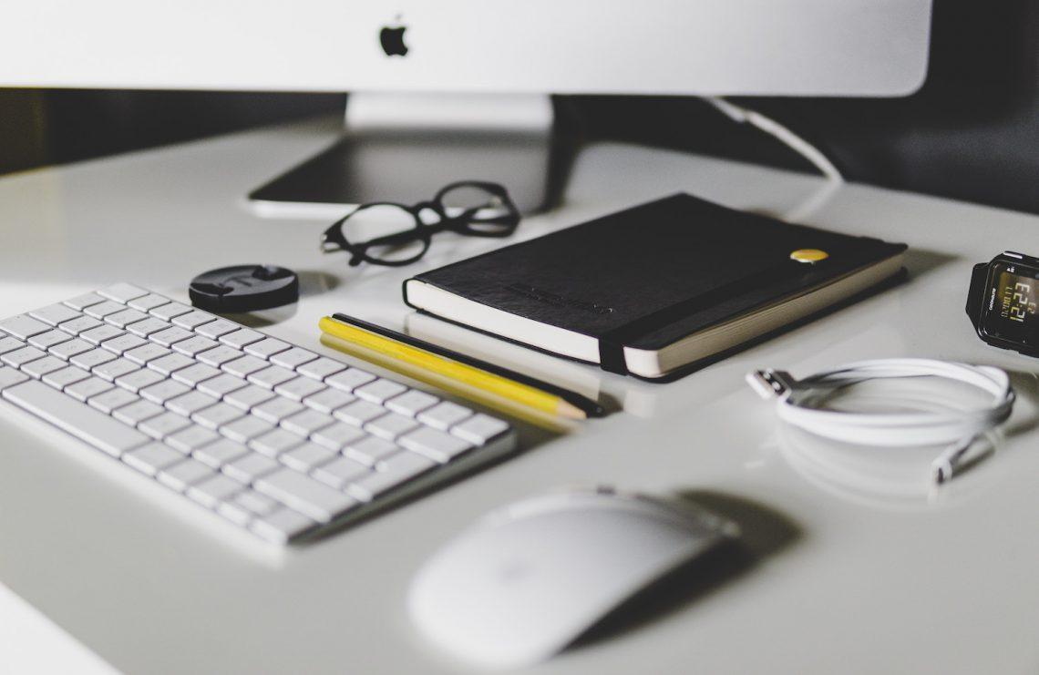 Ein Arbeitsplatz mit Tastatur, Stiften und Notizbuch als Symbolbild für die Arbeit von Lars Rademacher in PR und Lehre